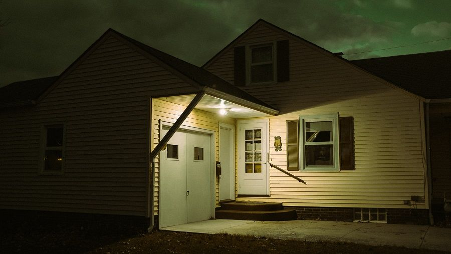 Front door of home well illuminated at night.